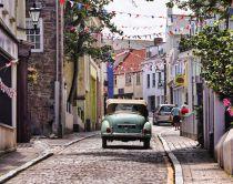 Vintage car driving down cobbled street with bunting, Alderney, Guernsey, Channel Islands, UK.