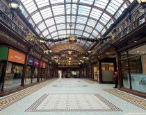 One man in an old-fashioned shopping arcade decorated with garlands at Christmas, Central Arcade, Newcastle Upon Tyne, Tyne and Wear, England