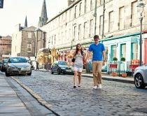 A day out in Edinburgh. A young couple, man and woman, shopping in the city. Holding hands. Carrying shopping bags. West End shops.