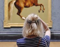 Woman looking at horse portrait in the National Gallery, London, England. Image has slight camera shake, this would show up on large printing.