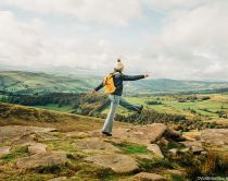 Woman skipping on rocks at Stanage Edge, Peak District, Derbyshire, England.