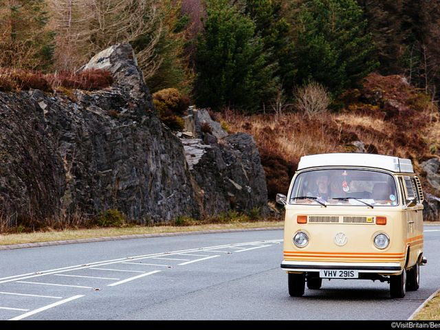 Vintage camper van driving along a country road in North Wales.