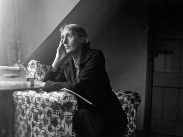 Virginia Woolf seduta ad una scrivania guardando fuori dalla finestra con mano accanto al volto