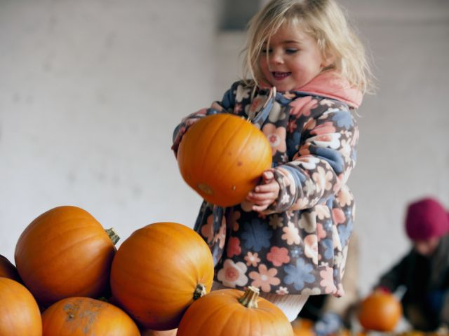 Girl playing with pumpkins at Halloween