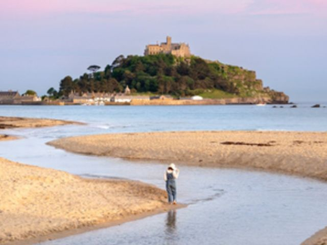 Girl exploring the beach of Marazion with St Michaels Mount in the background, Cornwall, England.