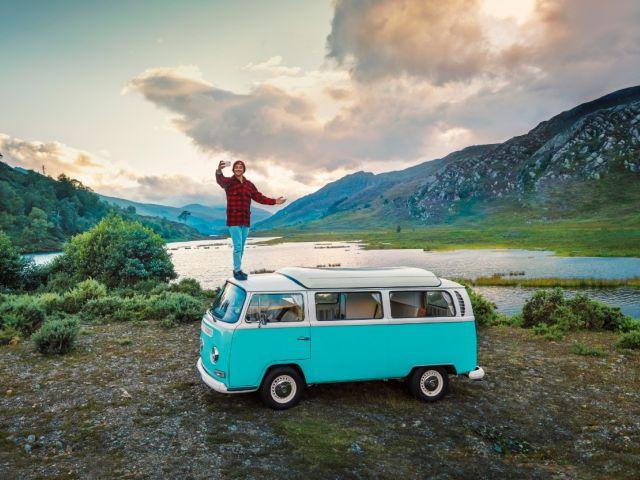 ragazzo in piedi su un van che fa un selfie con il panorama di giorno