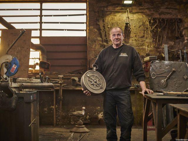 James Godbold met gesmeden klok in zijn werkplaats
