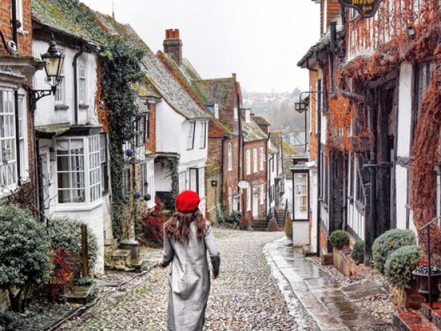 Woman walking down a cobbled street in Rye, East Sussex, England.