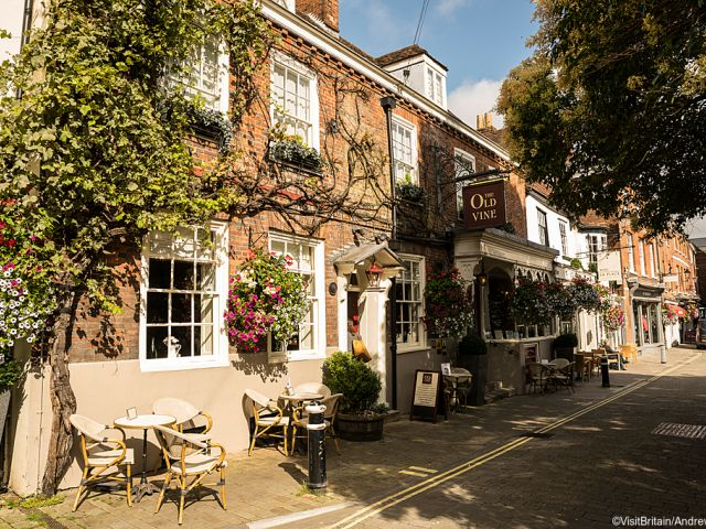 A winebar restaurant, the Old Vine, in Winchester, with tables and chairs outside. Summer flowers.
