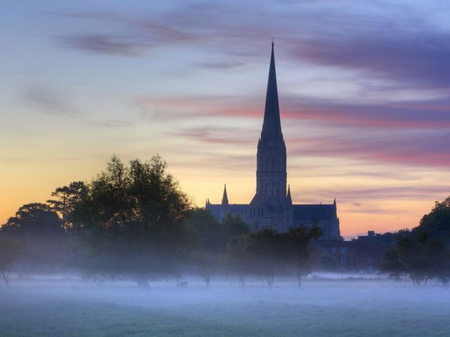 A misty field with a silhouette of a church in the distance in front of a sunrise