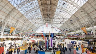 Inside Olympia London exhibition centre during an event with people in the main hall viewing exhibitors