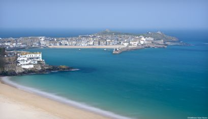 St Ives town and harbour viewed from above Porthminster beach. Calm turquoise sea water. Wide beach.