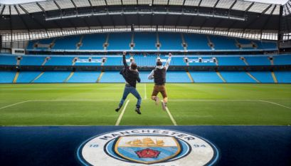 Two men jumping in the air at Manchester City football ground, the Etihad Stadium, Manchester, England. View from the terraces across the football pitch.