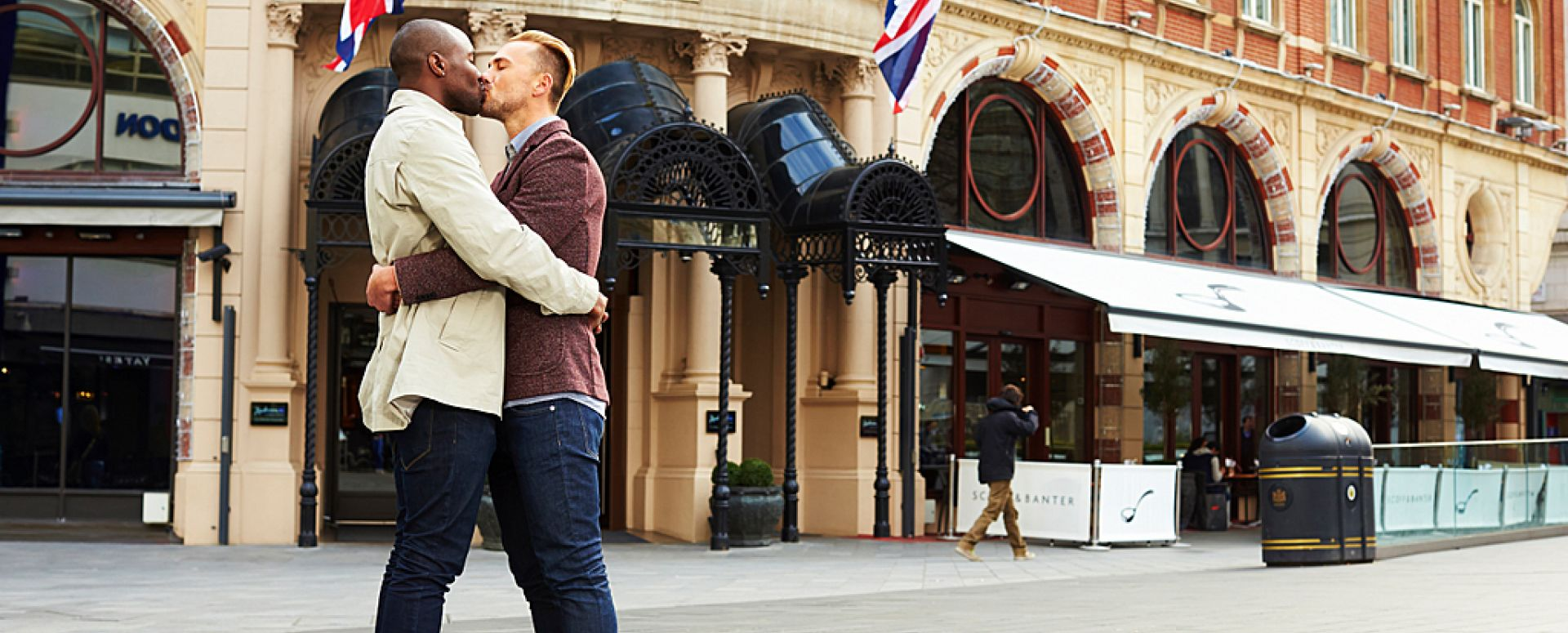 Love is GREAT. Gay couple embracing and kissing outside of The Hampshire Hotel, London.