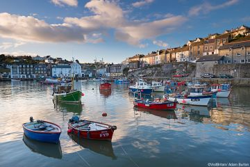 Dawn sky over Mevagissey village. A historic fishing harbour with a curving sheltering harbour wall. Flat calm sea. Boats moored. Houses on the hillside. South Cornish coast.