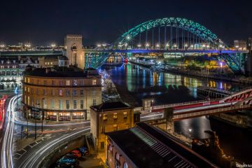 The Tyne Bridge, Swing Bridge and Sandhill, Newcastle-upon-Tyne, England at night.