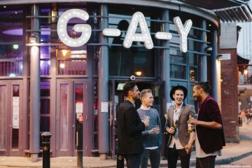 Love is GREAT. Group of gay couples standing outside G-A-Y Bar in Manchester. Smiling and holding drinks outside night club. Manchester nightlife.