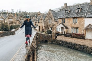 Woman balancing on bridge, Castle Combe, Wiltshire, England
