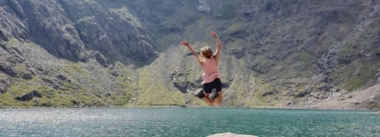 GIrl jumping into a lake, Snowdonia, Wales.