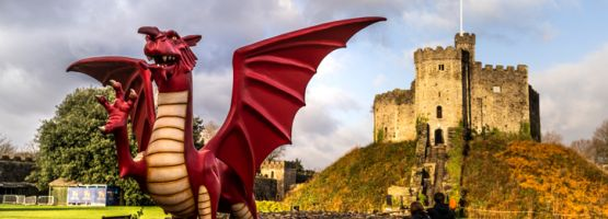 Cardiff Castle, a major visitor attraction, is a traditional castle with Roman foundations, Norman origins and Victorian additions. Dragon statue in foreground.