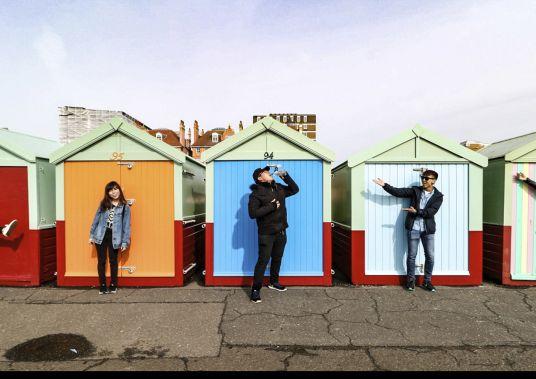 ragazzi in posa davanti alle cabine colorate di brighton