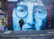 Young man standing in front of large John Lennon mural on brick wall in Bold Street, Liverpool, Merseyside, UK.