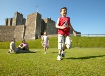 Boy running through the grounds at Rochester Castle on a sunny day.