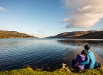 Молодая пара смотрит на Лох-Несс, Шотландия