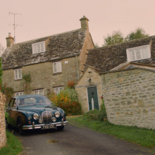 Classic car driving through tiny road in the Cotswolds