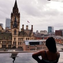 A woman looking at iconic buildings of Manchester from an rooftop pool