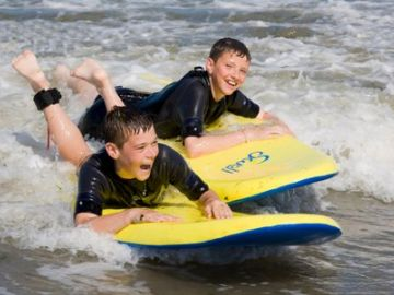 Kids bodyboarding in the UK sea
