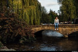 Blond woman wearing hat and jeans sitting on bridge in Bourton on the Water, Cotswolds, Gloucestershire, England, UK. ©VisitBritain
