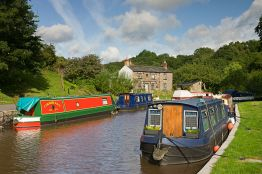 Narrowboats moored on the Monmouthshire and Brecon Canal at Llangattock village in the Brecon Beacons.