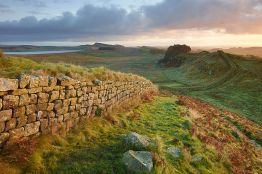 Hadrian's Wall near Housesteads. A section of the historic Roman stone wall fortification in Northern England started in AD 122. A UNESCO world heritage site. Sunrise or dusk.