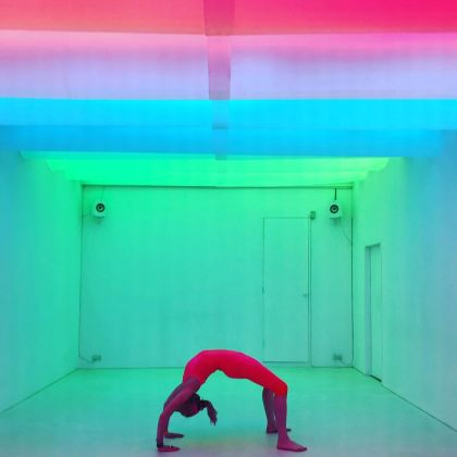 A woman performs a yoga move in Chroma Yoga's colourful studios