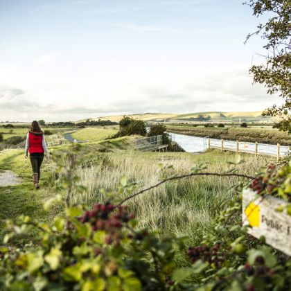 A woman in a red waistcoat on a footpath by water in the South Downs National Park.