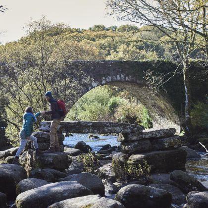 Couple climbing on boulders by a stream, Dartmoor National Park, Devon, England.