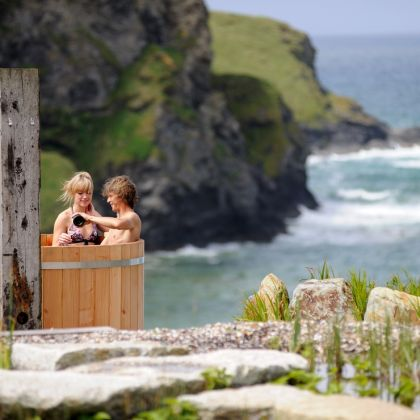 Guests enjoying a cliff top jacuzzi at The Scarlet hotel in Cornwall,