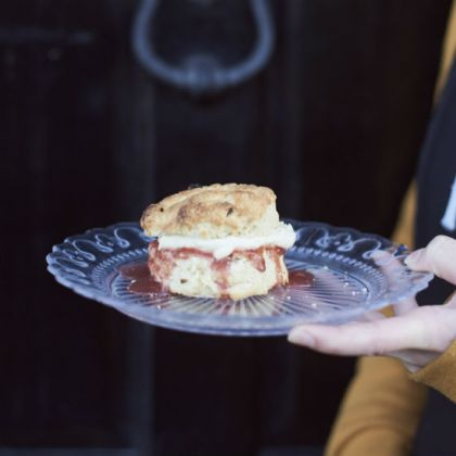 A hand holding a scone on a plate