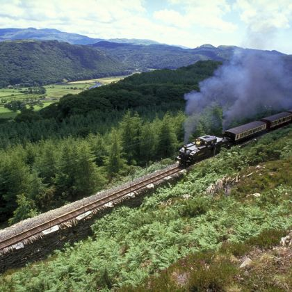 A Steam train travelling through the British countryside