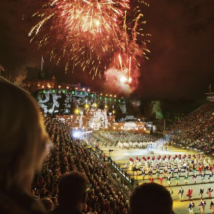 Edinburgh Tattoo, at Edinburgh Castle. Scotland. A view doiwn from the bleachers on to the parade ground. Fireworks in the night sky.