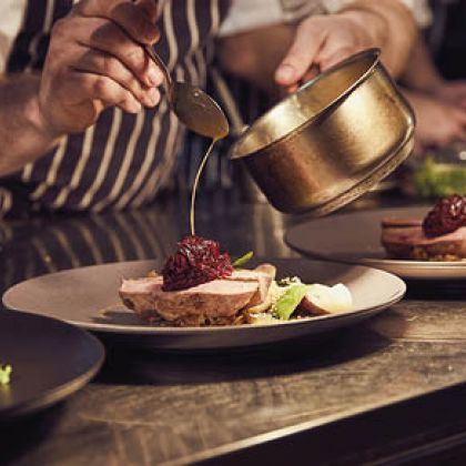 Restaurant in Edinburgh, Lothian, Scotland. Close up of chef standing at counter, holding saucepan, dressing plate of food.