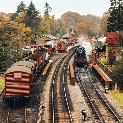 Steam train on train tracks and old-fashioned carriages at Goathland Railway Station, North York Moors, North Yorkshire, England.