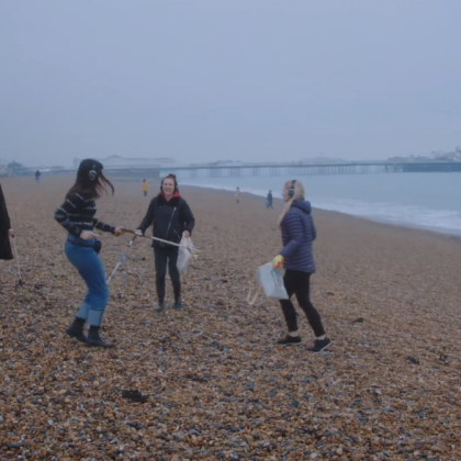 People dancing and litter picking on Brighton beach