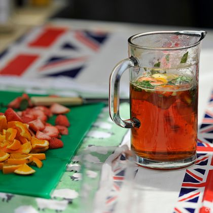 Pitcher of traditional summer drink Pimm's next to fresh chopped fruit and mint, the perfect refreshing addition to a British picnic.
