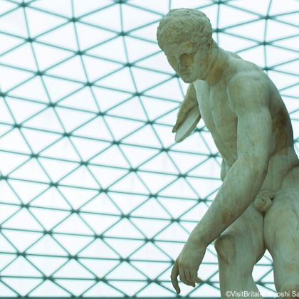 The British Museum Great Court with a modern glass roof. A statue of a discuss thrower the Townley Discobolus.