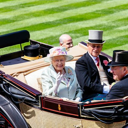 Royal Ascot Race Meeting at the prestigious Ascot racecourse in Berkshire. Royal Procession. Arrival of members of the Royal Family. Queen Elizabeth II and Prince Philip sitting in a horse-drawn carriage with two men, smiling and waving
