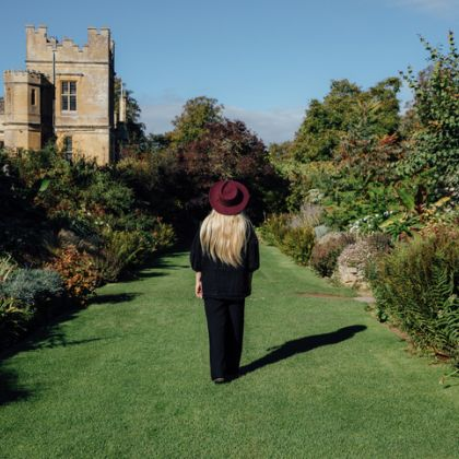 A woman walking in the gardens of Sudeley Castle & Gardens, Gloucestershire, England.