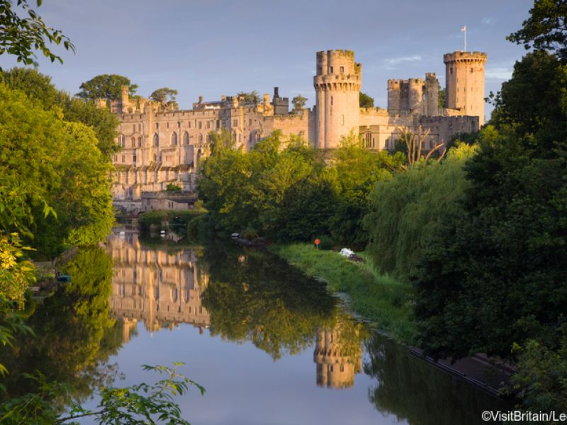 View of Warwick Castle, a medieval castle, from the River Avon. Grand imposing castle with medieval and Victorian buildings. River Avon.
