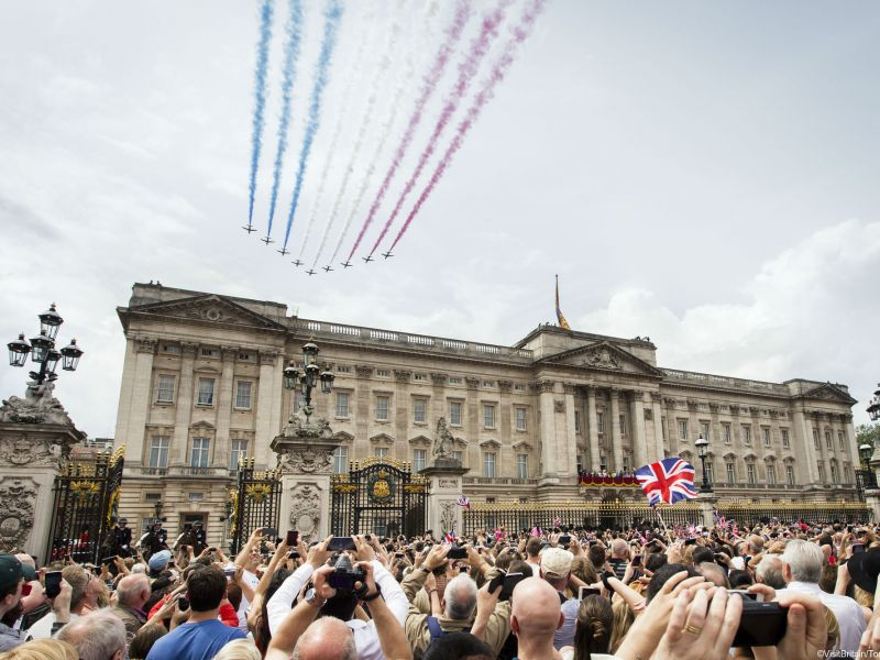 The Red Arrows aerial display team flypast over Buckingham Palace on a royal occasion and crowds in the Mall, London, England.